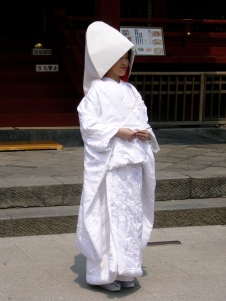 Clad in the traditional white hood and three-layered wedding kimono...