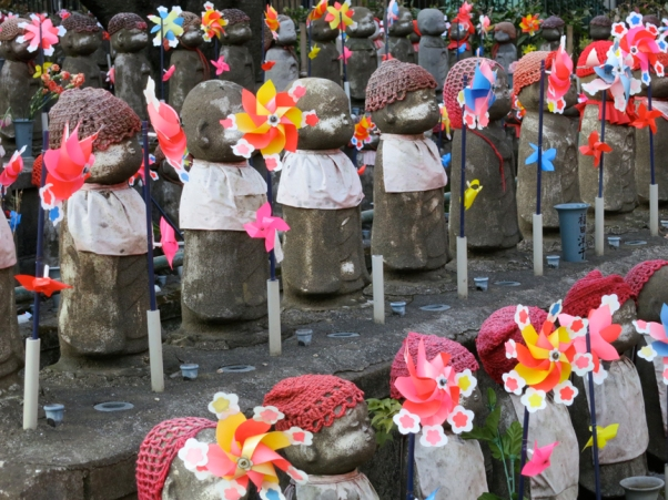 These o-Jizo-sama are dedicated to the souls of lost children, their pinwheels sending prayers to heaven with every breeze.