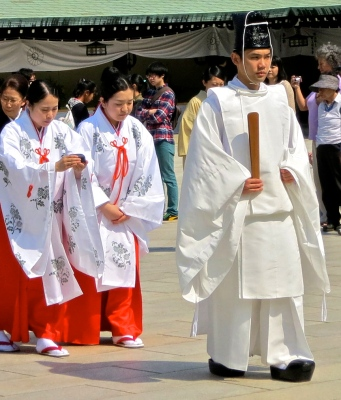 Shinto priests wear white linen robes, lacquered black mesh hats, and black clogs.