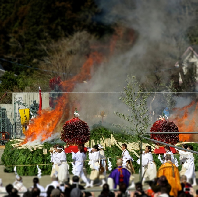 As the fire begins to catch, straw bales poked with thousands of arrow-like charms are paraded around the mountain of cedar. Afterwards, you can buy one to take home if you like.