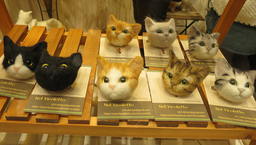 Scarily lifelike felted cat head pins.