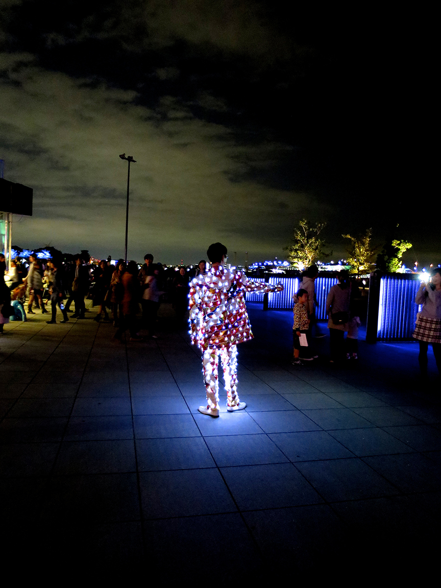 A crowd gathered nearby to watch a man in a fantastically illuminated suit. Wherever he walked, he took a little island of light with him.