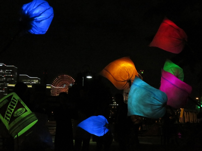 Lanterns made from odd materials float against the Yokohama skyline.