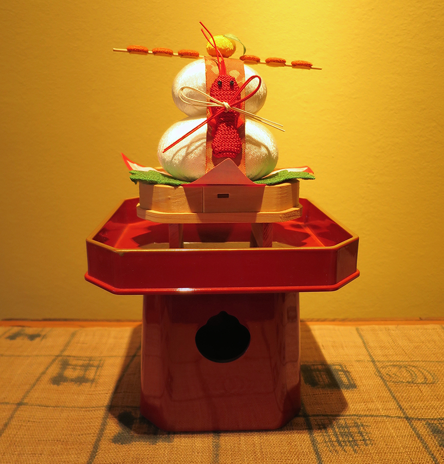 "The white things stacked on this lacquer stand are kagami mochi – ""mirror"" rice cakes that give a tip o' the beanie to the sun goddess who shut herself in a cave to pout, plunging the earth into darkness until she was lured out by catching a glimpse of herself in a mirror held up by a fellow goddess. (This is just a little fake one, but last year I posted a picture of the biggest real one I've ever seen here!)"