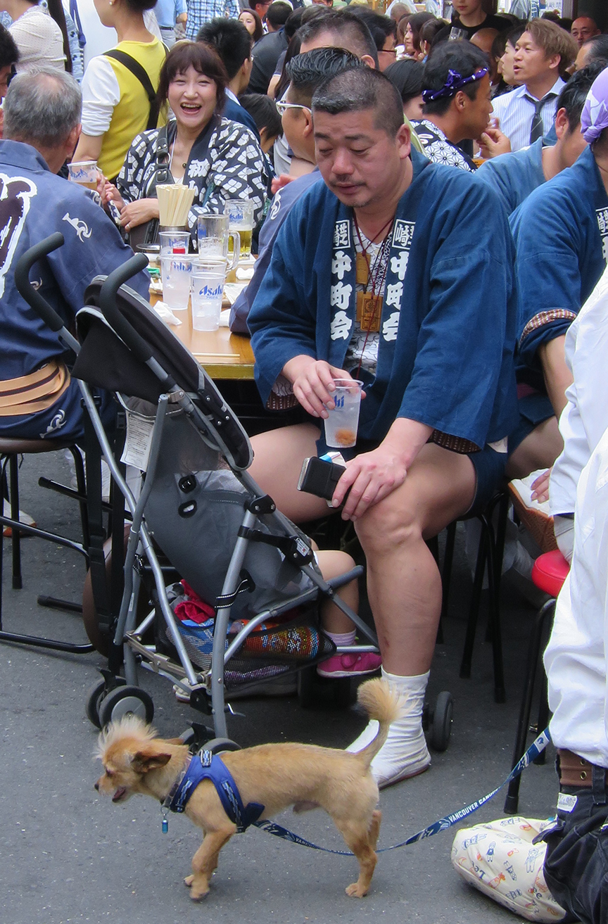 A tired shrine carrier relaxes after the festival with his mohawk-sporting poodle.