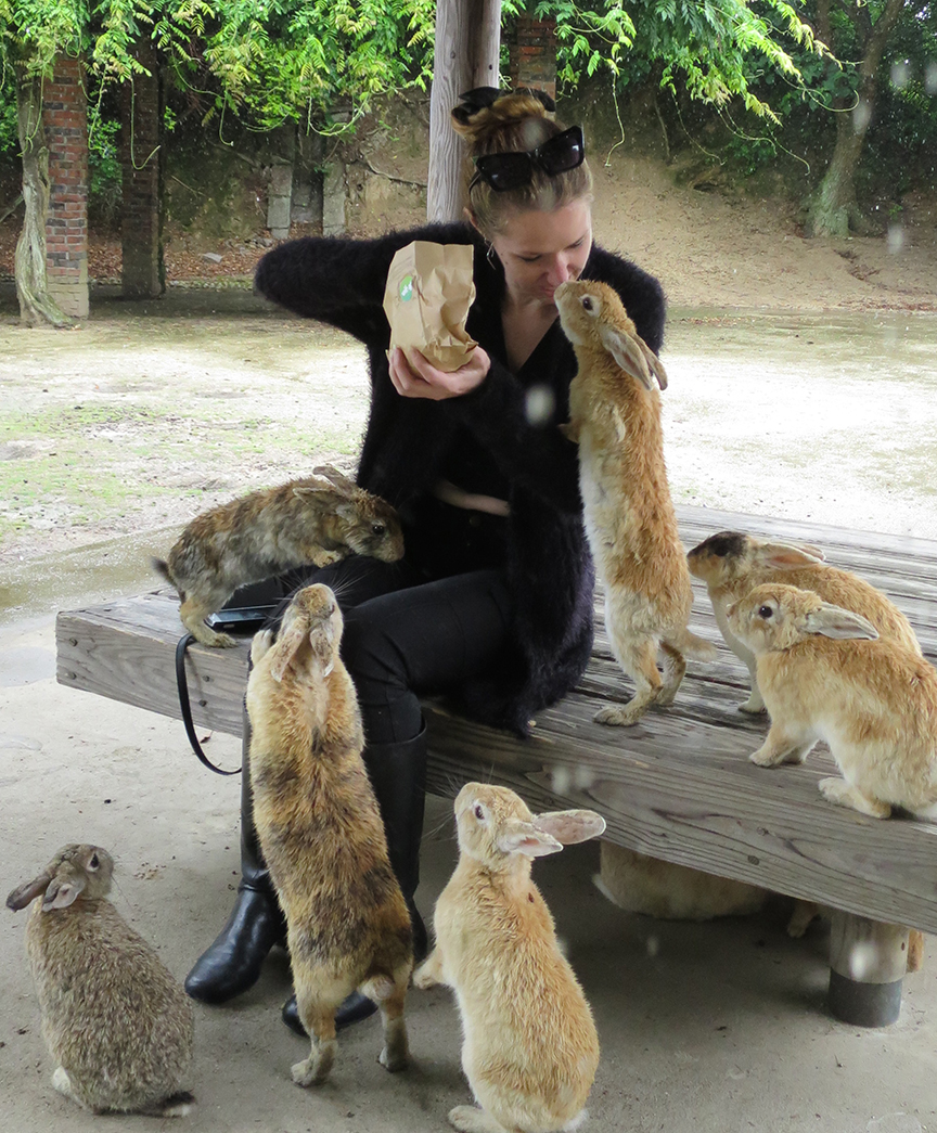 """In fact, """"not shy"""" hardly begins to describe these bunnies' attitude when it comes to mobbing rabbit-chow-dispensing humans. This is my friend Kendall, who will sadly never be able to enjoy a mere rabbit café again."""