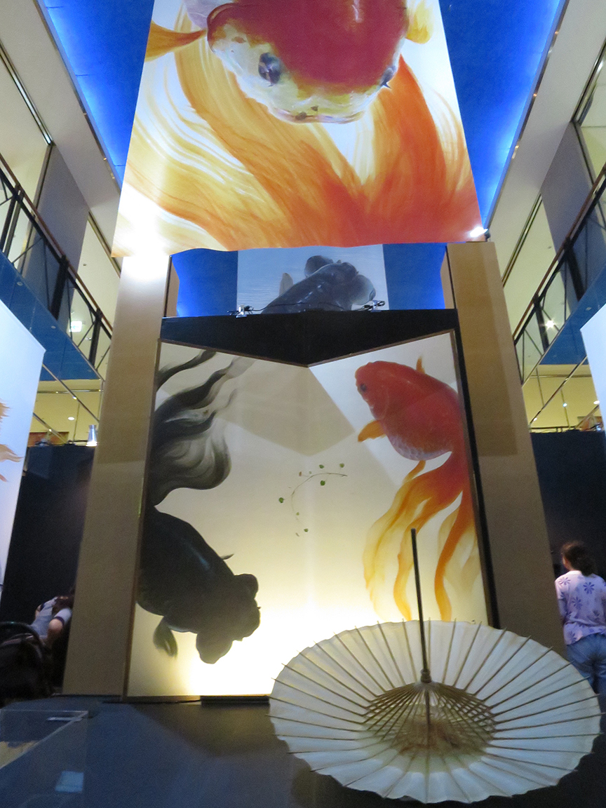 The exhibition entrance features his most recent works, larger-than-life goldfish painted with an enormous brush