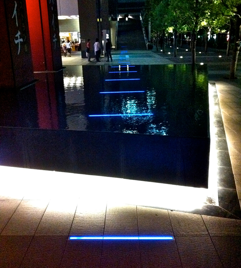 Blue neon lines art piece in Akihabara sidewalk and fountain