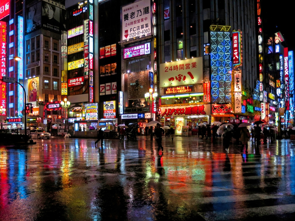 Kabukicho crossing lit up at night in the rain