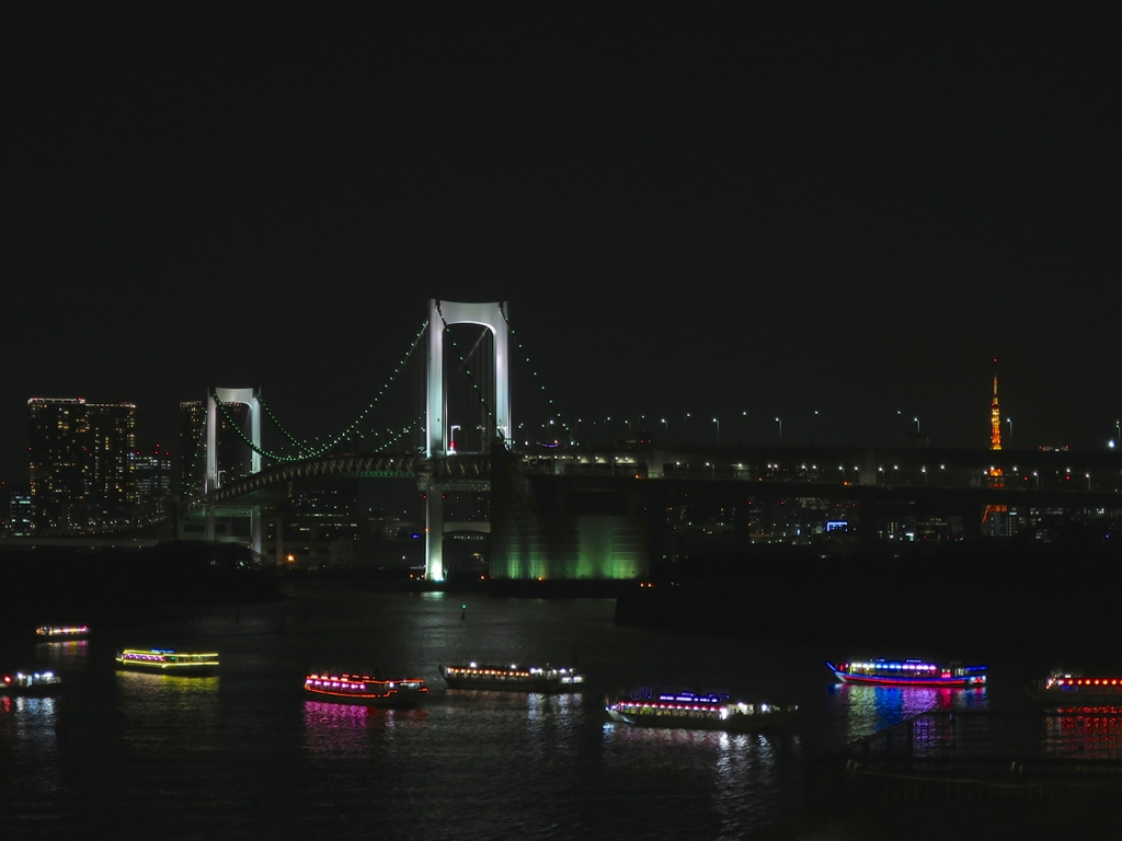 View of the Rainbow Bridge from Odaiba with many lit up pleasure boats