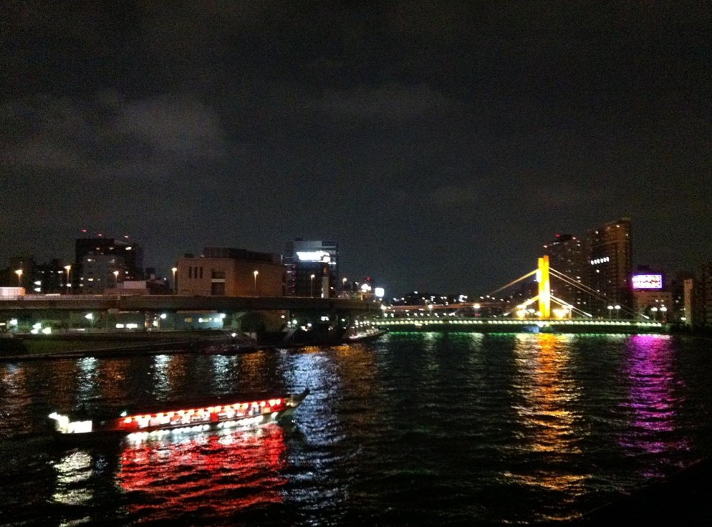 Sumida River bridge lit up at night with a pleasure boat