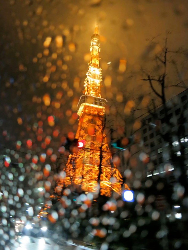 Tokyo Tower lit up at night in the rain