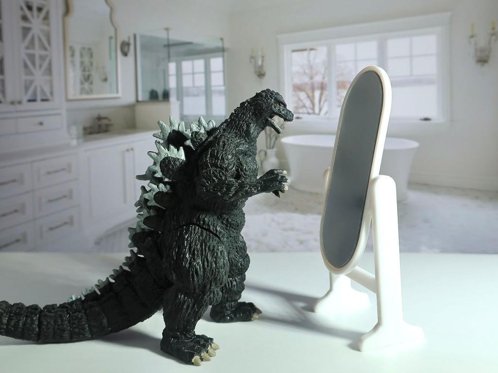 Japanese gachapon Godzilla toy looking in mirror