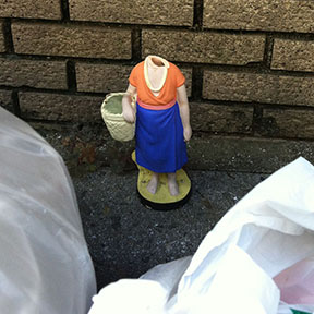 Headless plastic character figure with trash at Tokyo curb