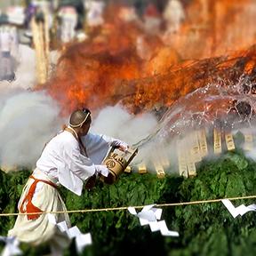 Monk throwing water on flames at Mt. Takao Hiwatari Matsuri