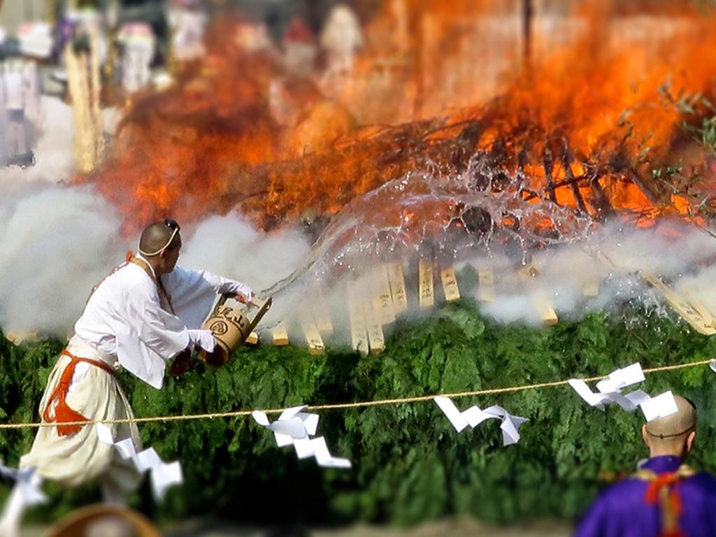 Monk throwing water on flames at Mt Takao Hiwatari Matsuri